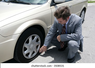 A man dressed for a business meeting discovering a flat tire on his car.