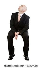 A man dressed in a business suit is sitting in a chair waiting.