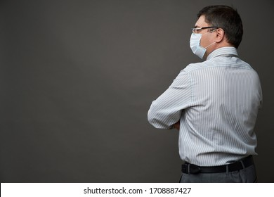 a man dressed as a businessman posing in a studio on a gray background, medical face mask, rear view, a light striped shirt and tie - casual office wear, concept of quarantine and antivirus protection