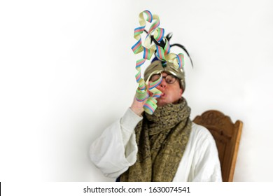 man dressed up for carnival, wearing a white robe, gold and blue coloured head dress and a shawl sitting in a chair blowing paper streamer (low depth of field). Only paper streamer is in focus.