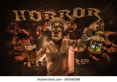 Man dressed as clown terrible captain with a mug of beer in his hand.