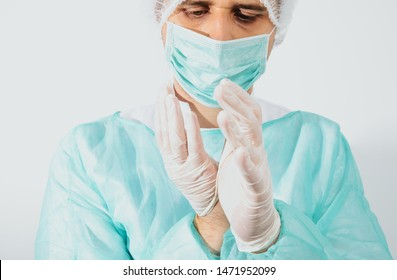 Man dressed in a green surgical apron and a mask on his face on a white background. Medical and pharmaceutical concept. Doctor or surgeon. Preparation for surgery, treatment of people.
