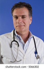 A man dressed in a lab coat with a stethoscope around his neck smiling a friendly smile.