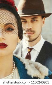 Man dressed like a gangster stands behind a woman in a hat