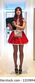 Man Dressed in Little Red Riding Hood. Beautiful sensual crossdresser posing in a skimpy Little Red Riding Hood costume with miniskirt. A man in a woman's dress. Sissy. Сrossdresser in dress with