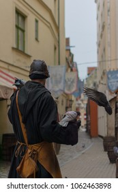 Man dressed in medieval clothes holding pigeons