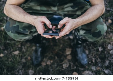 Man dressed in military clothes holding phone