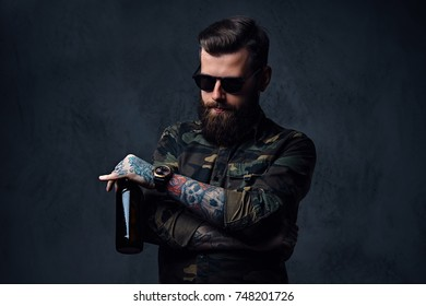 A man dressed in military shirt, drinks craft beer.