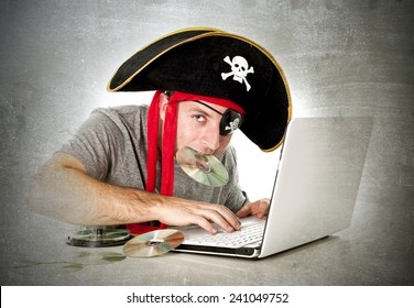 man dressed as pirate with CD in his mouth at computer laptop downloading music files and movies in copyright violation and illegal internet piracy concept