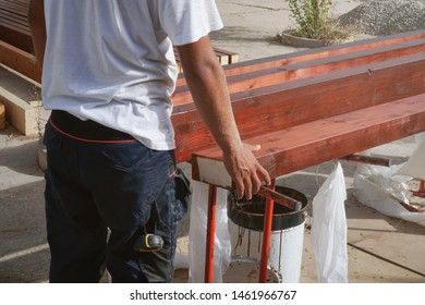 Man dressed in professional uniform is measuring and painting wooden piles for construction.Working labor concept.