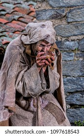Man, dressed in rags, begging through the streets of a village