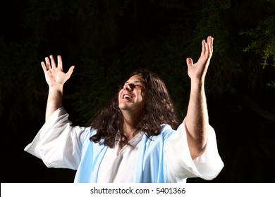 A man dressed in robe hands raised in the air praising or worshipping God
