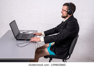 Man dressed in a suit and shorts siting with a laptop. The concept of remote work. Freelancer leading a video conference from home.