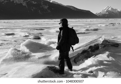 Man dressed in warm winter clothes near a frozen river in Alaska with huge ice chunks in black and white.