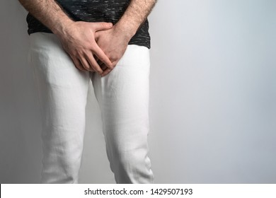 A man dressed in white jeans, holding hands on genitals. Disease for men. The concept of protection against sexually transmitted infections. Testicular cancer