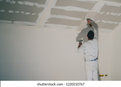 Man dressed in white, a painter, is applying putty or stucco to a dry wall installation in a house. Smoothing surfaces of a drywall application, reaching high up to the roof.