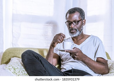 A man in dressed in white shirt is stiring his coffee with a spoon