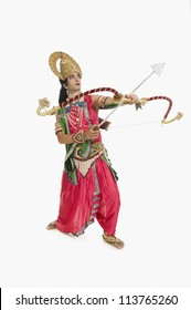 Man dressed-up as Rama and holding a bow and arrow