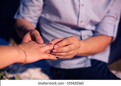 man dresses a ring on a finger to the girl