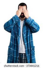 Man in dressing gown covering his eyes