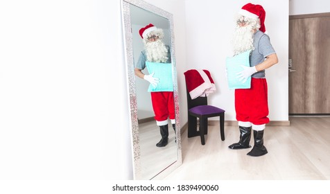 Man dressing up as Santa Claus, putting a pillow on his belly to look fatter, looking at himself in the mirror in the living room