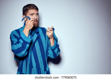 a man in a dressing-gown on a light background