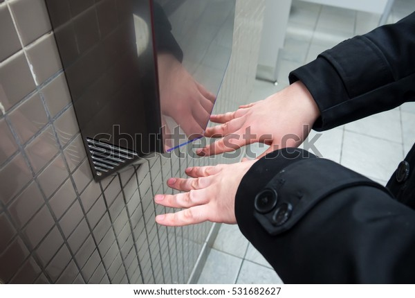 Man dries wet hands with an electric hand dryers
