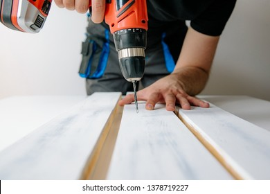 A man drilled by a drill in a wooden board. The concept of DIY and renovation of new things. A man tinkering at home, working with wood.