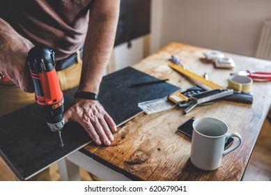 Man drilling laminate with power drill on the table