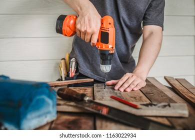 Man drilling wood with battery power Drill on the table in renovation work at home