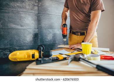 Man drilling wood with battery power Drill on the table at home