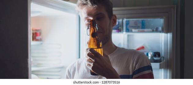 man drink bear from refridgerator at night time
