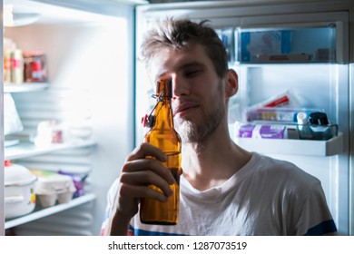 man drink bear from refridgerator at night time