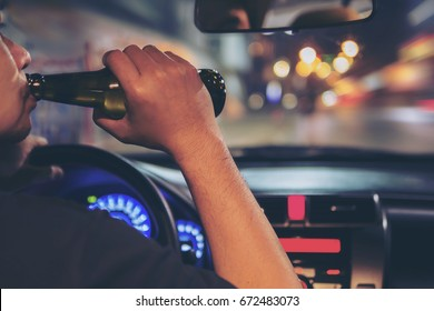 Man drink beer while driving at night in the city dangerously, left hand drive system