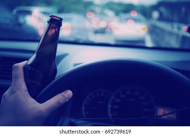 Man drink beer while driving car. Driving in a state of intoxication.don't drink and drive concept