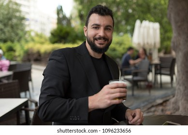 Man drinking beer in bar terrace looking at camera