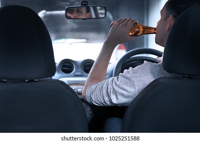 Man drinking beer and driving in a car.