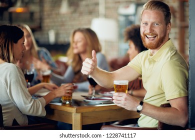 Man drinking beer and giving thumbs up while sitting in restaurant. In background his friends chatting and drinking alcohol.