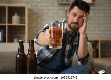 Man drinking beer at home. Concept of alcoholism