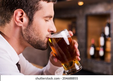 Man drinking beer. Side view of handsome young man drinking beer while sitting at the bar counter