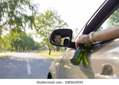 Man drinking beer while driving. Driving under the influence (DUI). Dangerous driver.
