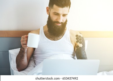 man drinking coffee in bed with laptop