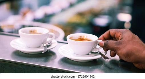 Mann trinkt Kaffeetasse allein an der Bar-Theke - Nahaufnahme von schwarzen männlichen Händen, die Espresso im Café hält - Lifestyle-Konzept der Menschen Alltagsgewohnheiten - Selektives Fokusbild