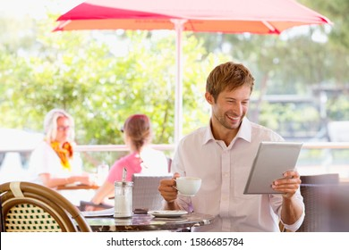 Man drinking coffee looking at digital tablet in outdoor caf_