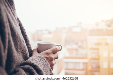 Man is drinking coffee on a balcony. Close up of hands with white cup of coffee. Early morning routine