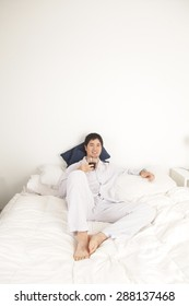 Man drinking a coffee on the bed