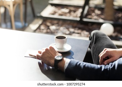 man drinking coffee in outdoor coffee shop