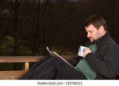 Man drinking coffee and reading a newspaper outside on a cool fall morning