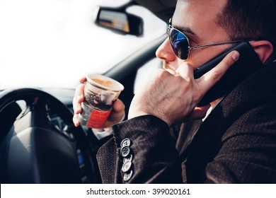 Man drinking coffee and using mobile phone while driving car