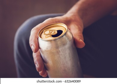 Man drinking a cold beer after work in the evening. Hand holding a aluminum can.